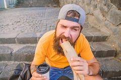 Better ingredients, better cuisine. Bearded man eating unhealthy fast food cuisine. Caucasian guy traveler enjoying stock image