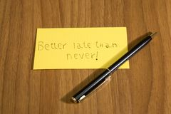 Better late than never handwrite on a yellow paper with a pen. Composition stock photos
