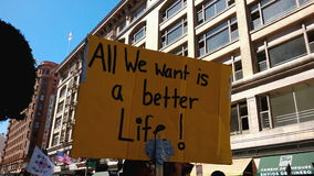 A Better Life Rally Sign. A large yellow picket sign that reads, 'All We Want Is A Better Life!' is held up during an immigration rally in downtown Los Angeles