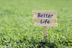 Better life sign. Better life wooden sign in grass,blur background stock photography