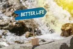 Better life sign board on rock. Better life wooden sign board arrow on rock , river and sun shine background stock photos