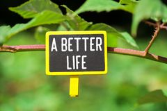 A better life on board. A better life written on yellow small chalkboard linked tree with clothespin on nature green background royalty free stock photo