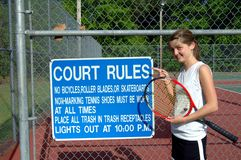 Better obey the rules!. Female teen poses besides the tennis court rules. She holds a red and black racket royalty free stock photo