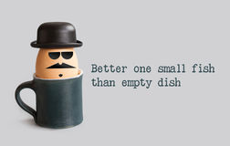 Better one small fish than empty dish. Proverbs metaphorical phrase and egg character with drawn gentleman face. Mustache, beard, black bowler hat, glasses Royalty Free Stock Photo