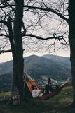 Better than any spa. Handsome young man lying in hammock and reading a book while camping with his girlfriend Royalty Free Stock Images