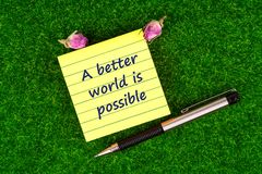 A better world is possible. In sticky note with pen and dried rose buds on grass Stock Photo