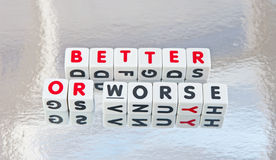 Better or worse. Text 'better or worse' in red and black uppercase letters inscribed on small white cubes, silver background Royalty Free Stock Images
