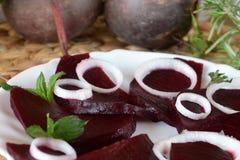 Betteraves organiques coupées en tranches fraîches à l'oignon décoré d'un plat blanc Images stock