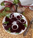 Betteraves organiques coupées en tranches fraîches à l'oignon décoré d'un plat blanc Photos libres de droits