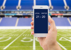 Betting in american football. Betting man through his smartphone in a american football stadium stock images