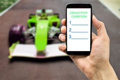 Betting on the car circuit. Betting man through his smart phone in a car circuit Royalty Free Stock Photography