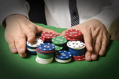 Betting on casino. Hands in foreground betting chips in a casino royalty free stock images