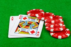 Betting chips and blackjack hand. Betting chips on a green card table with blackjack Royalty Free Stock Photography