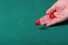 Betting on the odds. Dices being thrown in a craps game, or yatzee or any kind of dice involved game, Dices are a clear red color on a green felt table Royalty Free Stock Image
