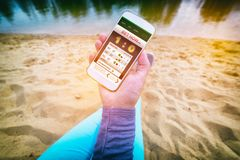 Betting on sports with smartphone. Betting on sports, hand holding smart phone with working online betting mobile application as a concept of gambling addiction stock images