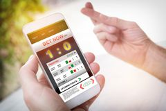 Betting on sports with smartphone. Betting on sports, holding smart phone with working online betting mobile application, crossed fingers used to wish for luck Royalty Free Stock Photography