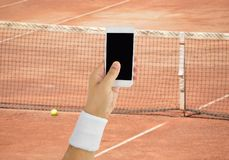 Betting on tennis. Man using mobile phone and betting during a tennis match Royalty Free Stock Photos