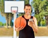 Betting and win. Fan of basketball is betting in internet with his smartphone over at outdoors Stock Photo