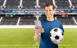 Betting and win. Football fan holding the ball and betting in internet with the smartphone at empty stadium in background Royalty Free Stock Photos