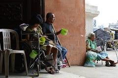 Bettler auf Rollstuhl neben dem Blinder, der Mobiltelefon am Kirchentür-Torportal verwendet Stockfotos