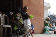 Bettler auf Rollstuhl neben dem Blinder, der Mobiltelefon am Kirchentür-Torportal verwendet Lizenzfreie Stockfotos