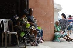 Bettler auf Rollstuhl neben dem Blinder, der Mobiltelefon verwendet Stockbild