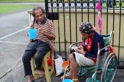 Bettler auf Rollstuhl unter Verwendung des Mobiltelefons Stockbilder