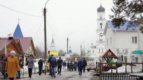 Bettler bitten um Geld nahe einem christlichen Tempel an einem bewölkten Tag des Frühlinges stock footage