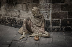 Bettler, der nahe einer Wand sitzt stockfoto