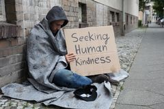 Bettler-Showing Seeking Human-Güte-Zeichen auf Pappe lizenzfreies stockfoto