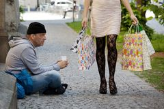 Bettler und wohlhabende Frau mit Einkaufenbeuteln Stockbild
