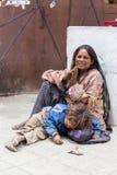 Bettlerfrau mit einem Kind, das im buddhistischen Tempel in Leh, Ladakh bittet Indien Lizenzfreie Stockfotos