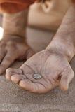 Bettlerhand mit Münze Lizenzfreie Stockbilder