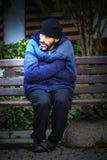 Bettlermann auf einer Bank Stockfoto