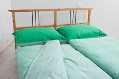 Bettwäsche in Grünem und in weißem Stockbild