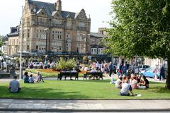 Betty's tea rooms. People sat down on the grass with the Famous Betty's tea rooms in the background, Harrogate, Yorkshire, UK Stock Image