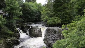 Betws-y-Coed Wales UK fast flowing river with white water flowing over rocks stock video footage