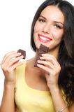 Beuaitiful smiling girl holding and eating chocolate isolated on Stock Images