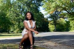 Beuatiful African American woman sitting next to road Stock Photos