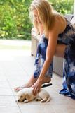 Beuatiful blonde woman with very young golden retriever puppy dog outdoor royalty free stock photos