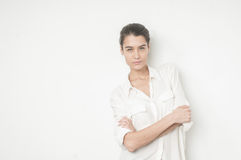 Beuatiful caucasian young woman with her arms on her chest. Beautiful confident caucasian girl on white background in white shirt stock images