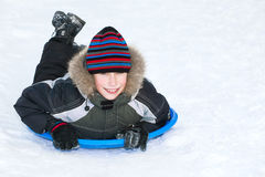 Beuatiful child wearing winter clothes sledding on snow. Having fun Royalty Free Stock Images