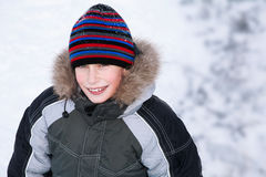 Beuatiful happy boy wearing winter clothes standing against snow background Royalty Free Stock Image