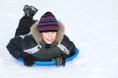 Beuatiful-Kindertragender Winter kleidet das Rodeln auf Schnee Lizenzfreie Stockbilder