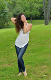 Beuatiful multiethnic woman in park in white tank and jeans Stock Photos