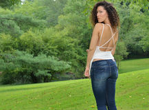 Beuatiful multiethnic woman in park in white tank and jeans Royalty Free Stock Photo