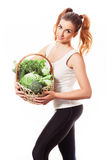 Beuatiful slim girl holding basket of fresh raw green vegetables on white background Royalty Free Stock Photos