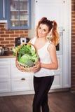 Beuatiful som ler den hållande korgen för flicka av nya grönsaker på modern scandinavian stilkökbakgrund Royaltyfri Foto