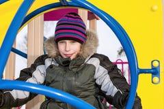 Beuatiful szczęśliwa chłopiec jest ubranym zimę odziewa bawić się przy kolorowym boiskiem obrazy stock