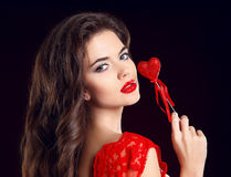 Beuaty Makeup. Beuatiful girl with red lips and Valentine heart. Isolated on black background stock photo
